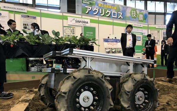 人の後ろを追従して収穫物を運ぶ自動走行ロボット(6日、名古屋市)
