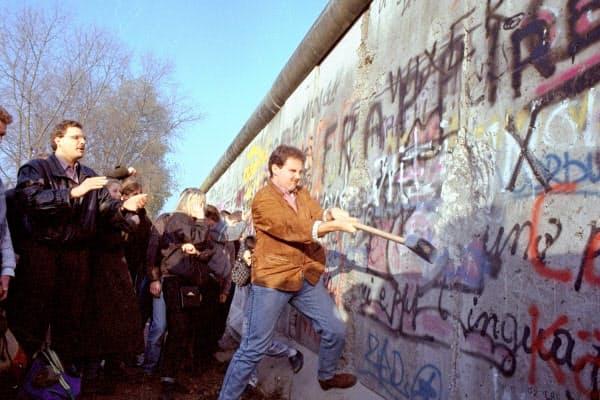 「ベルリンの壁」をハンマーで破壊する市民ら(1989年11月、ベルリン)=AP