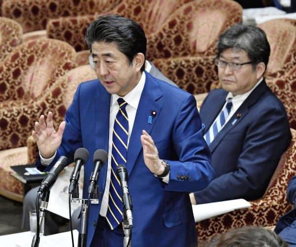 衆院予算委で答弁する安倍首相。奥は萩生田文科相(6日午後)=共同