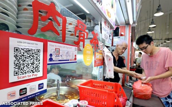 シンガポールのレストランでは決済アプリなどの案内が並ぶ=AP