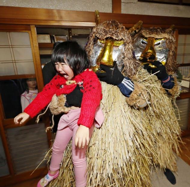 泣く子どもを抱きかかえるナマハゲ(秋田県男鹿市)