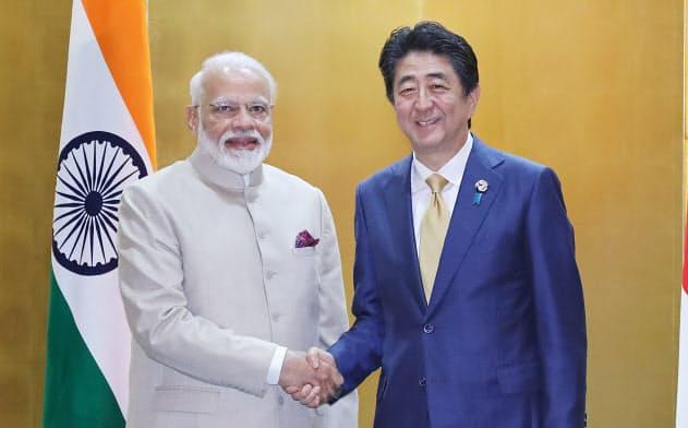 首脳会談を前に握手するインドのモディ首相(左)と安倍首相(6月、大阪市)