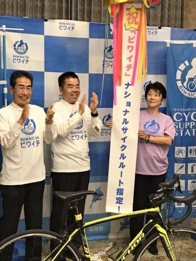 ビワイチのナショナルサイクルルート指定を受けて喜ぶ三日月大造知事(中央)=7日、滋賀県庁
