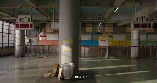 舞台のスクリーンには今春閉鎖されたあいりん総合センターの映像を映す=藤井 光撮影