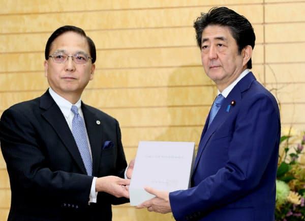 会計検査院の森田院長(左)から2018年度決算の検査報告書を受け取る安倍首相(8日午前、首相官邸)
