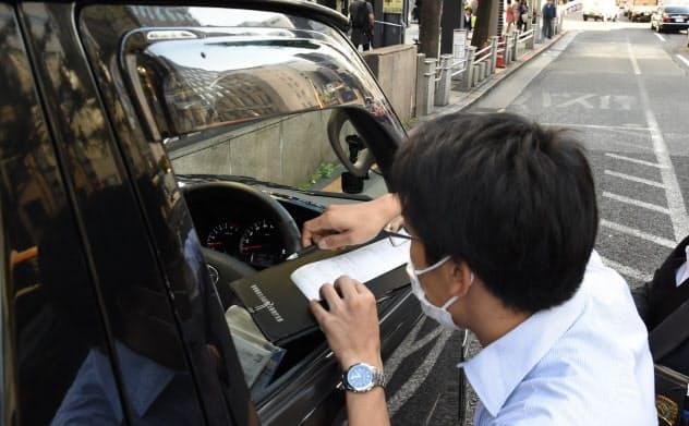 違法駐車を取り締まる警察官(10月30日、東京都中央区)