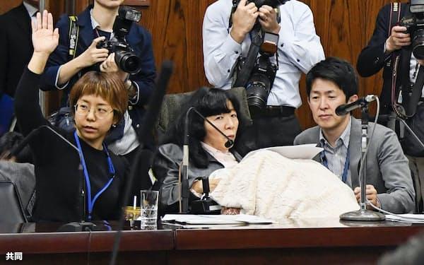 参院国交委でれいわ新選組の木村英子議員(中央)の質問のために挙手する介助者(5日午後)=共同