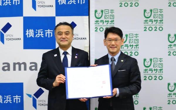 横浜市の小林一美副市長(左)と日本財団ボランティアサポートセンターの渡辺一利理事長が協定を結んだ(横浜市)
