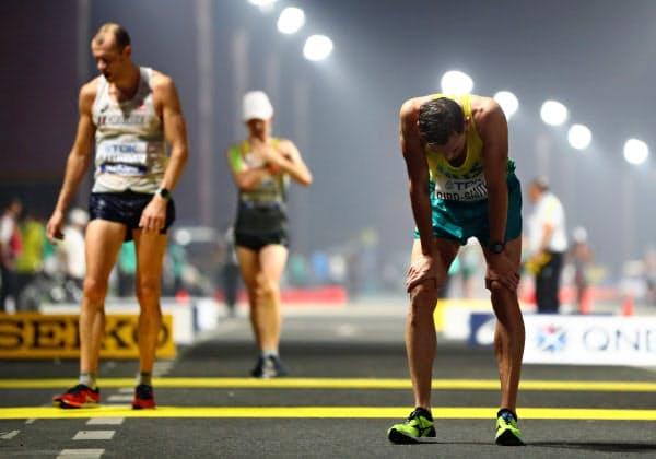 酷暑のドーハで開かれた世界陸上では途中棄権者が続出した(男子20キロ競歩でゴールした選手たち)=ロイター