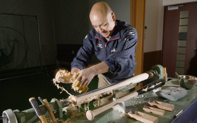 カンナやバイトと呼ぶ工具を使って木製バットを削り出す渡辺さん=目良友樹撮影