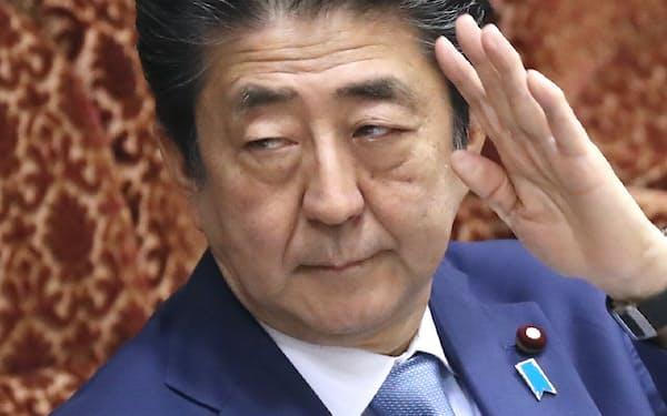 参院予算委で答弁のため挙手する安倍首相(8日)