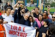 釈放後、「ルラは無実だ」と書かれた旗とともに支持者と撮影に応じるルラ氏(中)(8日、ブラジル南部クリチバ)=ロイター