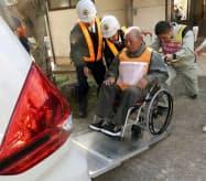 原子力総合防災訓練で、車いすのまま車両に乗り込む人(9日午前、松江市)=共同