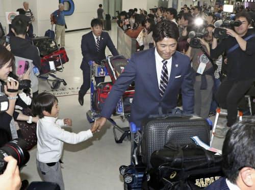 台湾から帰国し、子どものファンに迎えられる野球日本代表の稲葉監督(9日、成田空港)=共同