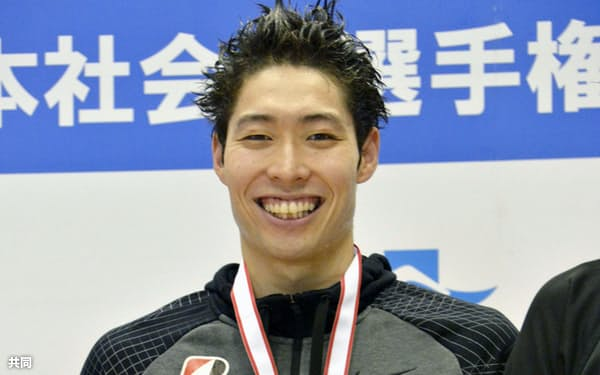 競泳日本社会人選手権の男子200メートル背泳ぎを制し、表彰式で笑顔の萩野公介(9日、静岡県富士水泳場)=共同