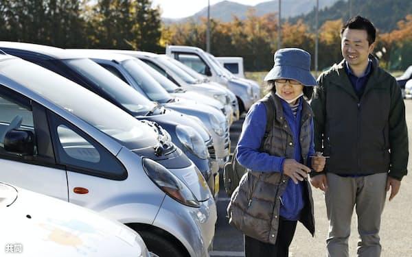 宮城県丸森町で車の無料貸し出しが始まり、日本カーシェアリング協会の職員(右)から説明を受ける女性(9日午前)=共同