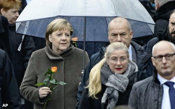 小雨が降るなか、ベルリンの壁崩壊から30年の式典に参加するメルケル独首相=AP