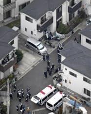 男性の遺体が見つかった民家(上)とその周辺を調べる捜査員(8日午後4時45分、東京都東久留米市)=共同