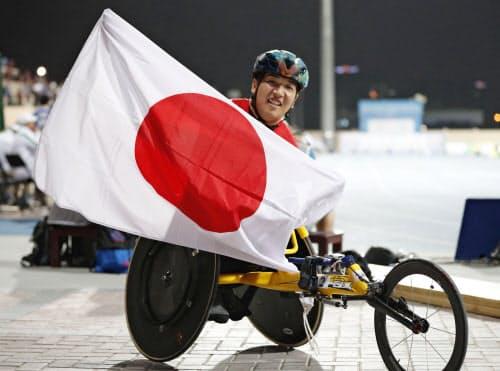 男子400メートル(車いす)で優勝し、日の丸を掲げる佐藤友祈。東京パラリンピック代表に内定した(9日、ドバイ)=共同