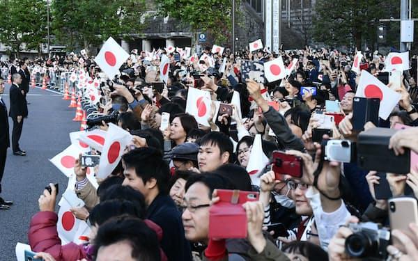 天皇、皇后両陛下に手を振る人たち(10日、東京都港区)