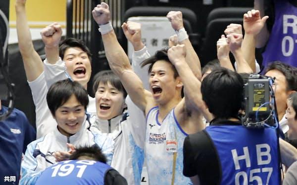 男子団体で初優勝し、喜ぶ萱和磨(中央)らセントラルスポーツの選手たち(10日、高崎アリーナ)=共同