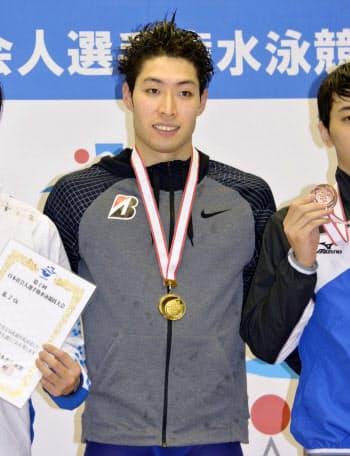 競泳の日本社会人選手権の男子200メートル個人メドレーで優勝し、表彰式で笑顔の萩野公介(10日、静岡県富士水泳場)=共同