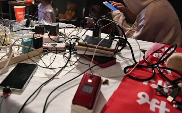 公民館で非常用電源から携帯電話に充電する人たち(9月11日、千葉県君津市)