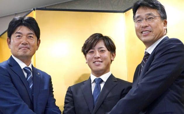 入団が決まり、日本ハムの大渕スカウト部長(右)らと握手するJFE西日本の河野竜生投手=中央(11日、広島県福山市)=共同