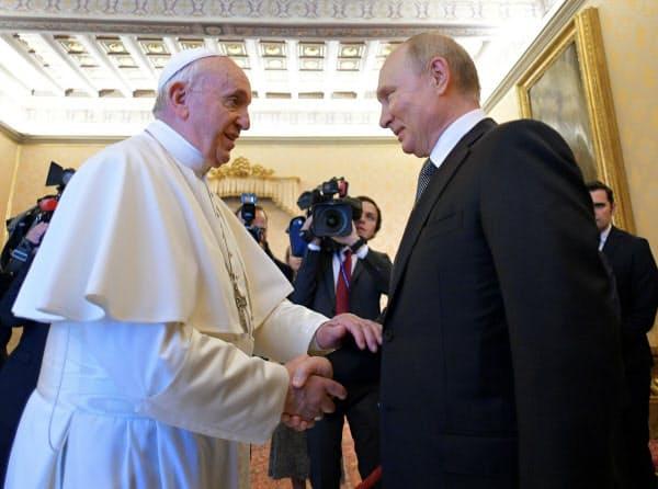 ロシアのプーチン大統領(右)と握手するローマ教皇(7月、バチカン)=ロイター