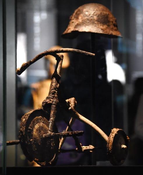 原爆で焼け焦げた三輪車とヘルメット(広島平和記念資料館・鉄谷信男氏寄贈)=藤井凱撮影