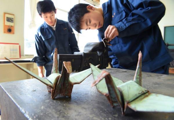 市内の聖堂で使われていた銅板で、ローマ教皇に贈る折り鶴を作る佐藤匠さん(左)ら(広島市立工業高校)=藤井凱撮影