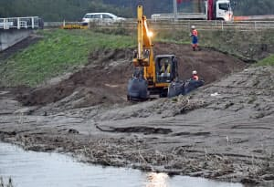復旧作業が進む決壊した堤防(10月18日、宮城県丸森町)