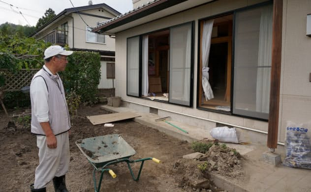 宮城県丸森町飯塚地区の佐久間さん。浸水被害の片付けが続く日々に疲れた表情を見せた(7日)