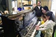 台風19号の影響で浸水被害を受けたピアノに触る鈴木智子さんと子どもたち。奥は調律師の遠藤洋さん(10月、福島県いわき市)=共同