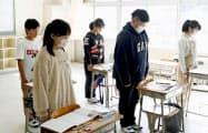 間借りして授業を受けている丸森小の教室で黙とうする金山小の児童(12日正午、宮城県丸森町)=共同