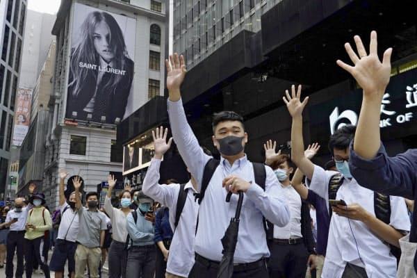 金融街で手を開いて「五大要求」を求める人たち(12日、香港)=AP