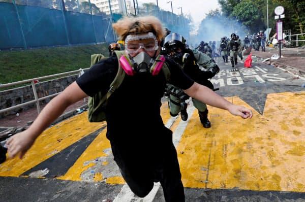 12日、香港中文大学のキャンパスで警察に追われて逃げる学生=ロイター