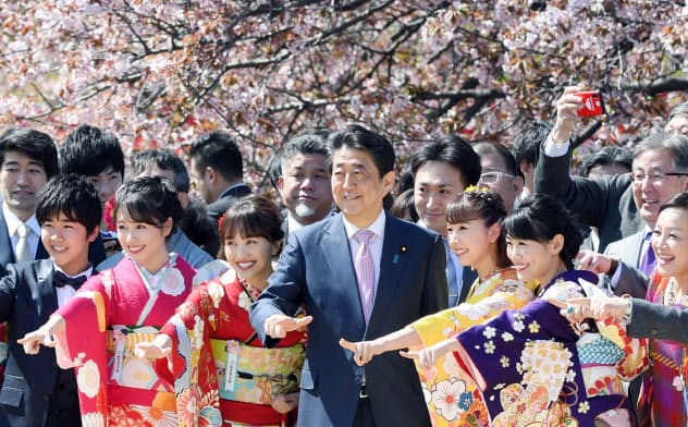 桜を見る会で参加者と記念写真に納まる安倍首相(4月13日、東京・新宿御苑)