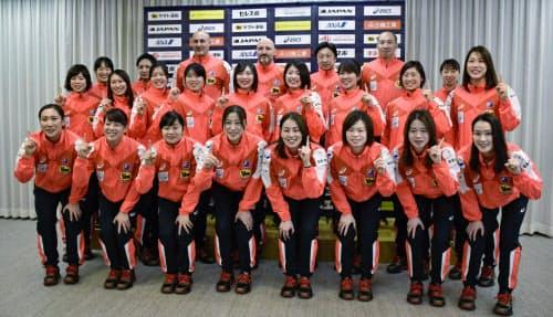 ポーズを取るハンドボール女子の日本代表メンバー(12日、東京都内)=共同