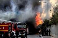 パレスチナ自治区ガザからのロケット弾攻撃を受け、炎上するイスラエルの工場(12日)=AP
