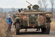 9日、兵力の引き離しが始まったドネツク州でウクライナ軍の装甲車両に近づくOSCEの停戦監視員=ロイター