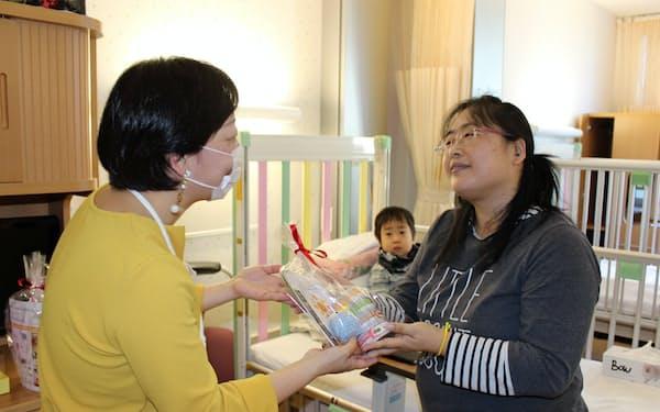 NPO法人から缶詰を受け取る母親(5日、佐賀大病院)
