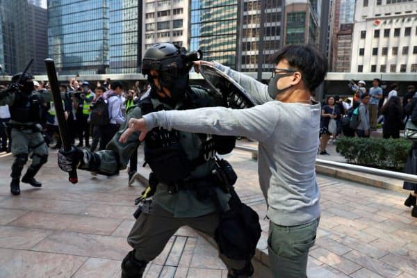 金融街・中環では平日昼間から警官隊とデモ隊が衝突した(13日、香港)=ロイター
