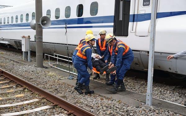 緊急停止した列車からけが人を担架で運び出す訓練も行った(13日、静岡県三島市)