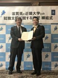 就職支援協定を結んだ滋賀県の三日月大造知事(右)と近畿大学の細井美彦学長(13日、滋賀県庁)