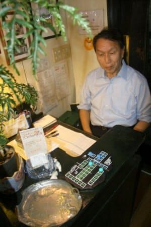 田中さんはスタッフと交代で受け付けに座る