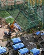 台風15号の影響で倒壊したゴルフ練習場の鉄柱の撤去作業(13日、千葉県市原市)=共同通信社ヘリから