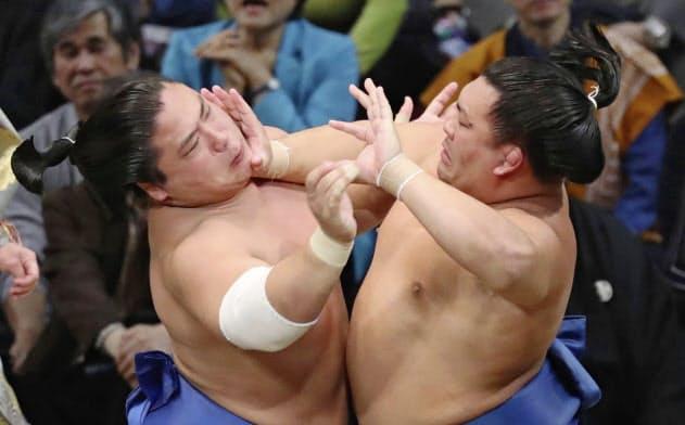 照強(右)を攻める若隆景。勝負を決めた後、土俵下に落ちて負傷した(13日、福岡国際センター)=共同