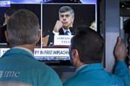 ウクライナ疑惑の公聴会中継を見るニューヨーク証券取引所の関係者ら(13日)=AP