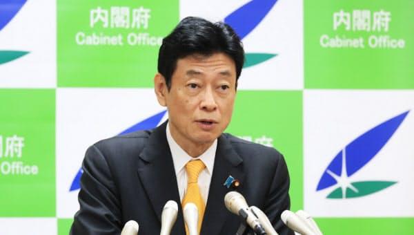記者会見する西村経財相(14日、内閣府)